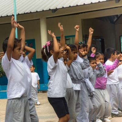 Teenage volunteers working with children in Ecuador lead a session on the playground.